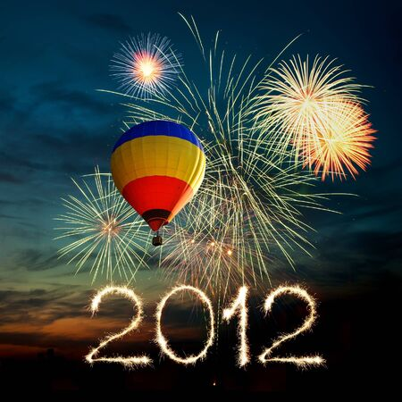 Nieuw jaar 2012. helder en kleurrijk vuurwerk en hete lucht-ballon van verschillende kleuren in de nachtelijke hemel bij zonsondergang