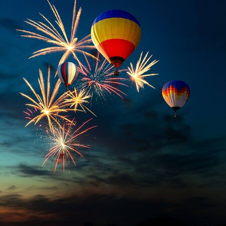 fire show: bright colorful fireworks and hot air-balloon of various colors in the night sky at sunset