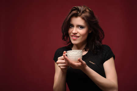 beautiful woman with cup of tea or coffee on a red background photo
