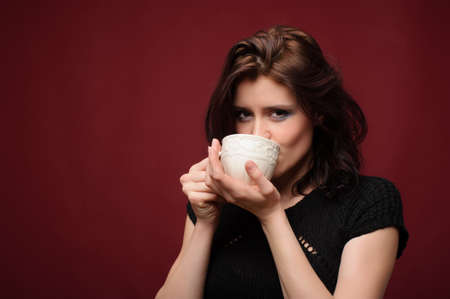 beautiful woman with cup of tea or coffee on a red background Stock Photo - 12406842