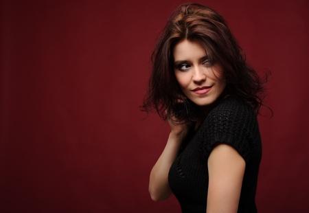 pelo castaño claro: Mujer joven linda sobre un fondo rojo Foto de archivo