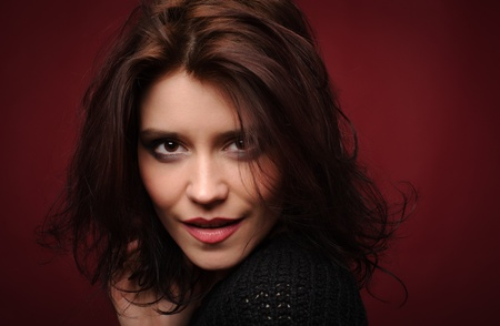 ojos marrones: Mujer joven linda sobre un fondo rojo Foto de archivo