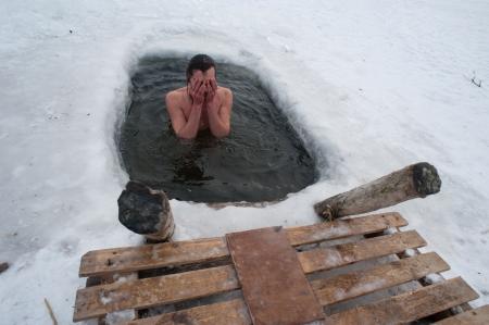 De winter zwemmen man in het ijs-gat Stockfoto