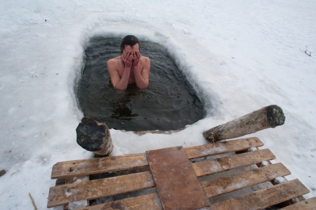 The winter swimming  man in the ice-hole
