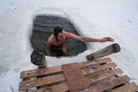 A téli úszás férfi a jeges-lyukú