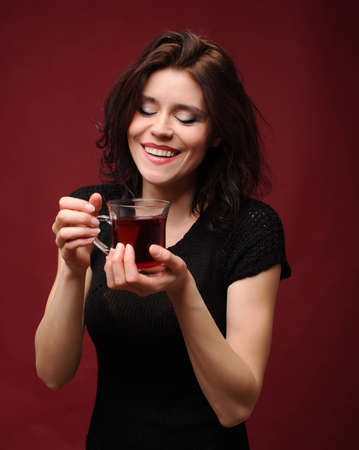 beautiful woman with cup of tea on a red background photo