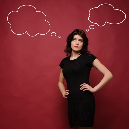skeptic: attractive young woman thinking, studio red background