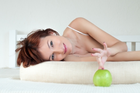 Portrait of an attractive young woman with an green apple at bed Stock Photo