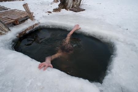 De winter zwemmen. man in het ijs-gat.
