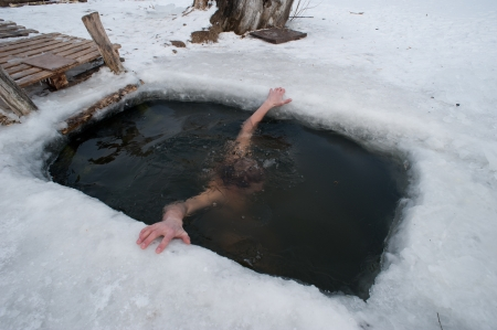 frozen lake: The winter swimming. man in the ice-hole.