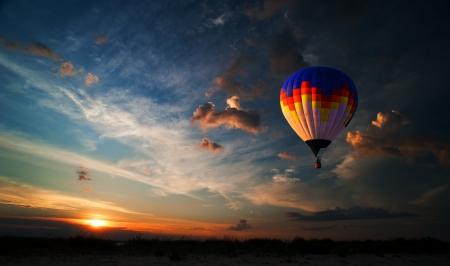 Kleurrijke hete luchtballon vliegt bij zonsopkomst