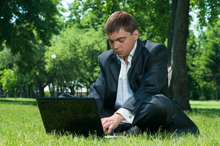 Business man sleeping on the job at a laptop on the grass photo