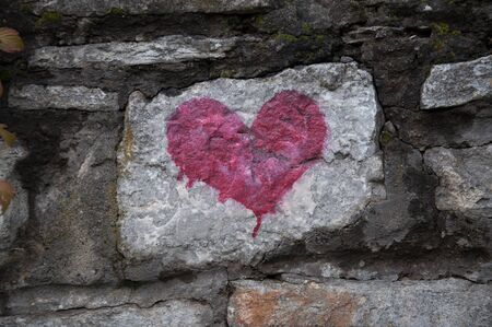vandal: red heart - love symbol on old stone wall