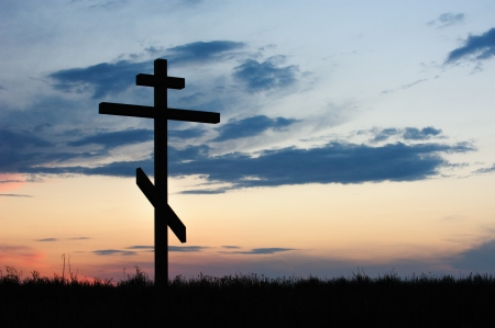 tortured: cross silhouette with the sunset as background