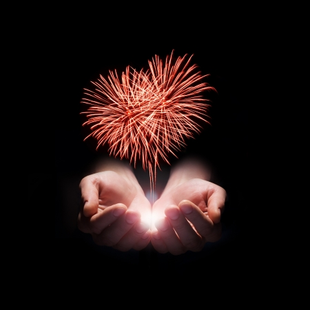 fireworks in the mens hands in the shape of a red heart on black background Stock Photo