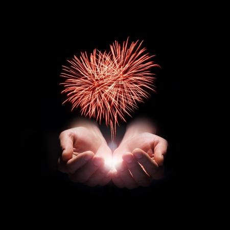 vuurwerk in de mannen handen in de vorm van een rood hart op zwarte achtergrond