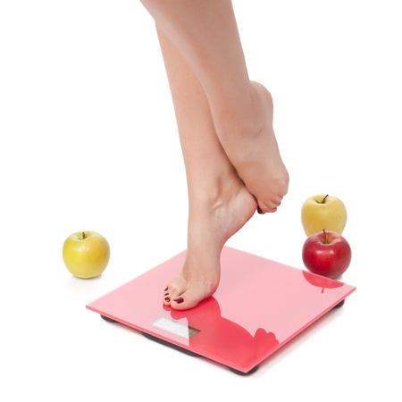 Woman perfect shaped legs on scale with apple on white background