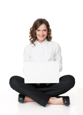 Portrait of a pretty young woman sitting in front of her laptop isolated over a white background photo