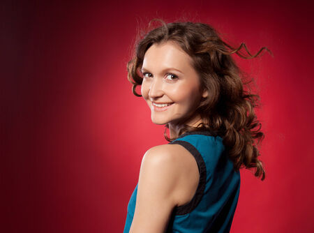 Portrait of a pretty young woman on a red background photo
