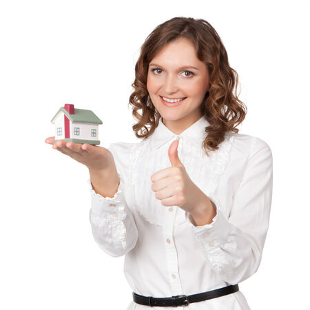 Beautiful young woman holding house model over white - real estate loan concept photo