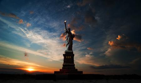 일출과 흐린 하늘의 배경에 자유의 여신상