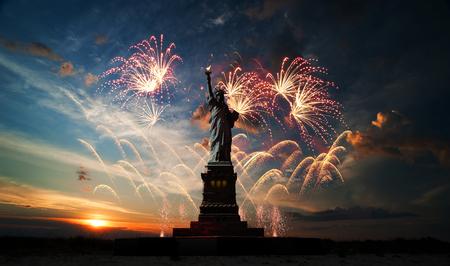 日の出と花火のためのバック グラウンドで自由の女神像 写真素材