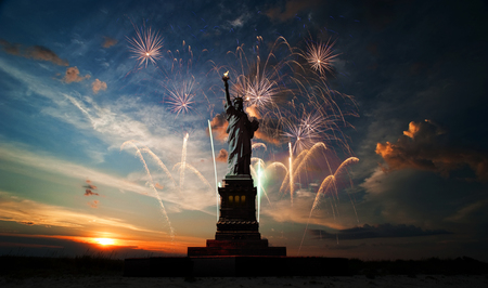 Statue of Liberty on the background of sunrise and fireworks photo