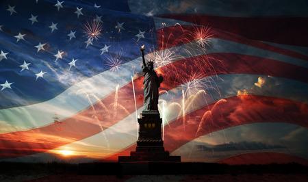 バック グラウンドで自由の女神像フラグ米国、日の出と花火 写真素材
