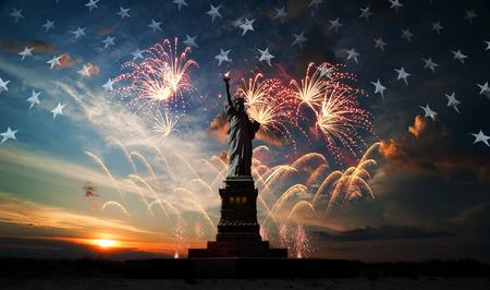 Standbeeld van Liberty op de achtergrond van de vlag usa, zonsopgang en vuurwerk Stockfoto