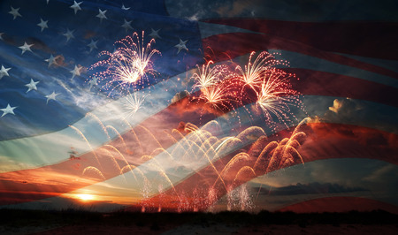 fourth of july: Celebratory fireworks on the background of the US flag and sunrise. Independence day