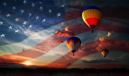 Kleurrijke ballonnen vliegen bij zonsopgang op de achtergrond van de vlag van de VS Stockfoto