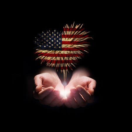 검정색 배경에 미국 국기와 심장 모양에서 남성의 손에 불꽃 놀이 스톡 콘텐츠