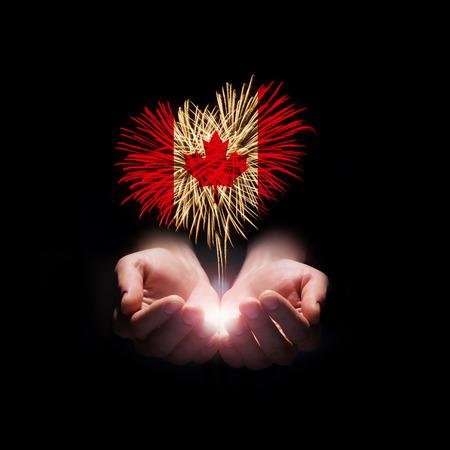 캐나다에 검은 색 캐나다 데이에 오신 것을 환영에 캐나다 국기와 함께 심장 모양에서 남성의 손에 불꽃 놀이 스톡 콘텐츠