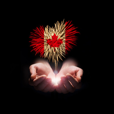 Fireworks in male hands in a heart shape with the Canada flag on a black background  Canada day  Welcome to Canada