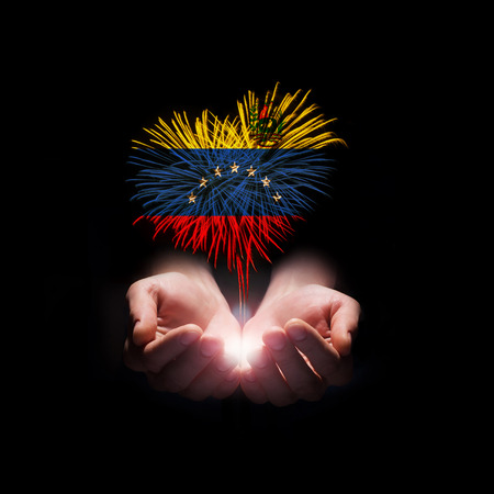 Fireworks in male hands in a heart shape with the flag of Venezuela Stock Photo