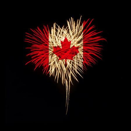 黒い背景にカナダの国旗とハートの形で花火