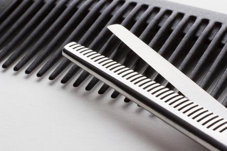 cabello negro: tijeras para operaci�n peluquer�a y un cepillo para el cabello en blanco Foto de archivo