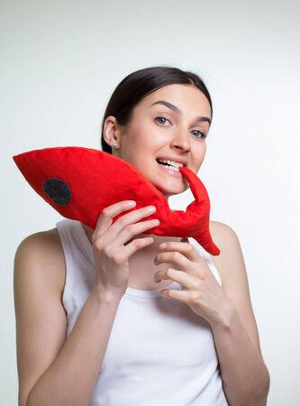 흰색 배경에 빨간 장난감 물고기와 젊은 여자 스톡 콘텐츠