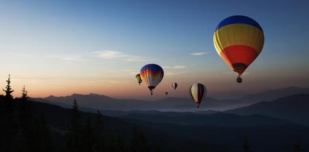 다채로운 뜨거운 공기 풍선 일출 산에서 날고있다