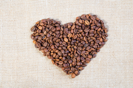 cheerfulness: Heart from brown coffee beans on burlap light