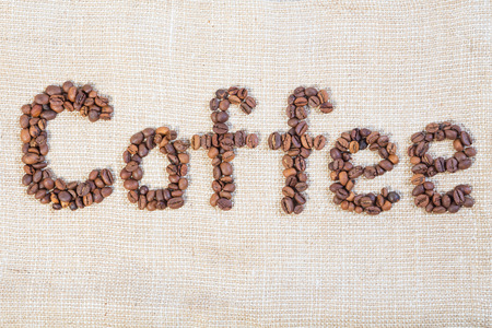 joyfulness: Word coffee made from coffee beans laid out in the light sacking Stock Photo