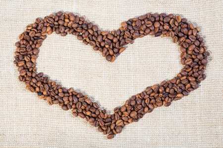 cheerfulness: The border in the form of heart from brown coffee beans on the bright burlap