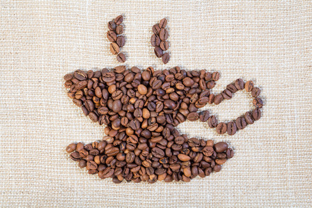 cheerfulness: Cup of brown coffee beans on burlap light