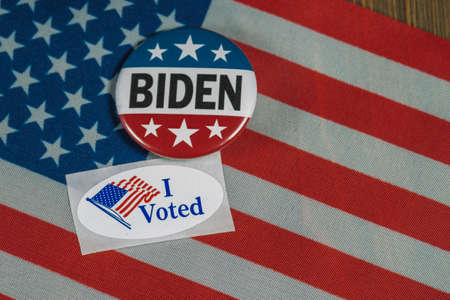 Washington DC--July 5, 2020; Round red white and blue Joe Biden campaign button next to oval shaped I Voted sticker on American flag and wooden table top Editorial