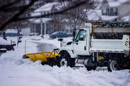 View of white and yellow city snow plow truck driving away while removing fresh deep snowfall in winter in suburban area to make roads safe for drivers