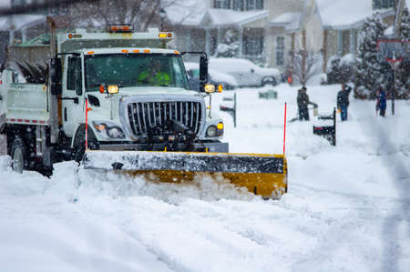 Front right view of city services snowplow truck clearing roadways of snow after winter storm covered streets in urban area