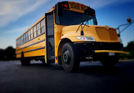 Low angle view of the front door side entrance of a yellow American public school bus used to transport kids to school, field trips and extra circular events such as sports teams.