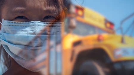 Composite image of young girl with concerned look wearing face mask required for students during COVID-19 pandemic in front of yellow public school bus