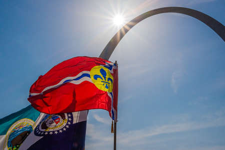 Saint Louis city, Missouri state and department of the interior flags fly in front of silhouetted Gateway Arch national park with summer sky in the background
