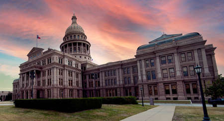 View of the Texas State Capitol building with domed roof made of Sunset Red Granite stone at dusk with pink and orange colored sky Stock fotó